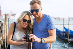 Couple looking at photos on back of digital camera Royalty Free Stock Images
