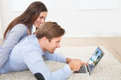 Couple looking photos on laptop at home Stock Photos