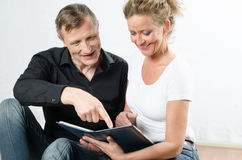 Couple looking at photos sitting on the floor.  Stock Photos