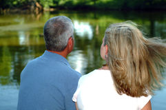 Couple Looking at Pond. Married couple looking out over the pond with the wind blowing her hair Stock Image