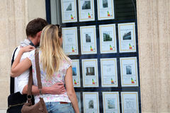 Couple looking at real-estate ads in the street. Couple looking at house-for-sale ads through shop window royalty free stock photo