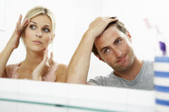 Couple Looking At Reflections In Mirror For Signs Of Ageing Stock Image