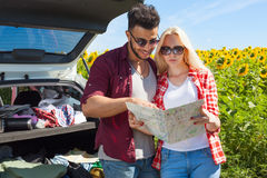Couple looking road map standing sunflowers field outdoor Royalty Free Stock Photography
