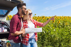 Couple looking road map standing sunflowers field outdoor Stock Images