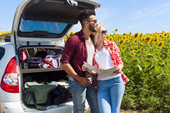 Couple looking road map standing sunflowers field outdoor Royalty Free Stock Images
