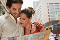 Couple Looking In Roadmap. Happy couple looking at road map with arm around Royalty Free Stock Image