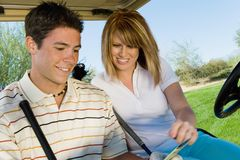 Couple Looking At Scorecard. Happy couple looking at scorecard while sitting in golf cart Stock Images
