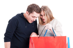 Couple looking in shopping bags and being surprised Stock Photos