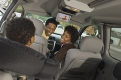 Couple Looking At Small Boy In Car. An African American couple looking at small boy in car Stock Image
