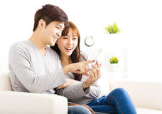 Couple Looking at smart phone In living room Royalty Free Stock Image