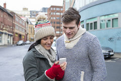 Couple looking at a smartphone in the city Stock Photography