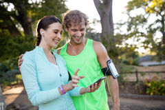 Couple looking at smartphone while jogging. On a sunny day Royalty Free Stock Photo