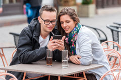 Couple looking on smartphone while sitting at coffee shop table Stock Photos