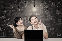 Couple looking at solution light bulbs in class Royalty Free Stock Photos