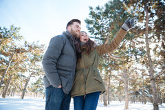 Couple looking on something in winter park Stock Photo