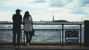 Couple Looking at Statue of Liberty stock images