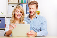 Couple looking on tablet computer stock image