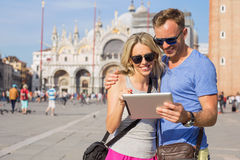 Couple looking at tablet computer while traveling in Venice Stock Photo