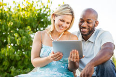Couple looking at tablet PC stock photography
