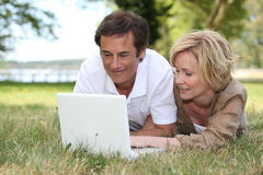 Couple looking at their laptop. In a park Stock Photo