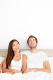 Couple looking thinking in bed stock images