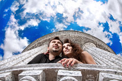 Couple looking to the future. Beautiful couple hugging and looking to the future on balcony with column at blue dizzying sky background Stock Image