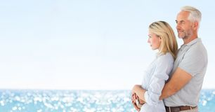 Couple looking to left against blurry beach Royalty Free Stock Photos