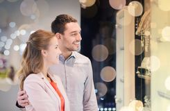 Couple looking to shopping window at jewelry store. Sale, consumerism and people concept - happy couple pointing finger to shopping window at jewelry store in stock photography