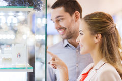 Couple looking to shopping window at jewelry store. Sale, consumerism and people concept - happy couple pointing finger to shopping window at jewelry store in royalty free stock photography