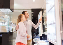 Couple looking to shopping window at jewelry store. Sale, consumerism and people concept - happy couple pointing finger to shopping window at jewelry store in Royalty Free Stock Image