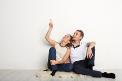 Couple looking up, sitting on floor. In new apartment, dreaming about future, men point upward, copy space Royalty Free Stock Photo