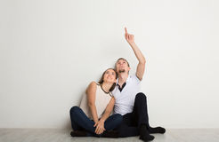 Couple looking up, sitting on floor. In new apartment, dreaming about future, men point upward Royalty Free Stock Images