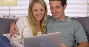 Couple looking for vacation getaway on laptop. On couch Royalty Free Stock Photo