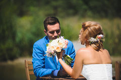 Couple Looking at Wedding Bouquet. Bride and groom looking at wedding bouquet Stock Photography