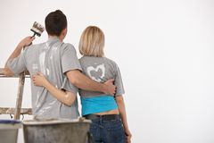 Couple looking at white wall after painting Royalty Free Stock Photography