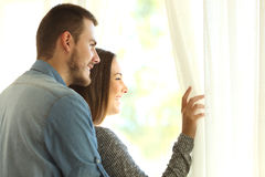 Couple looking through a window Royalty Free Stock Image