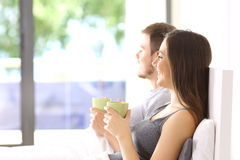Couple looking through a window in the bedroom Royalty Free Stock Images
