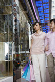 Couple Looking At Window Display For Shopping. Young couple with shopping bags looking at window display Royalty Free Stock Images