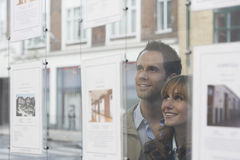 Couple Looking Through Window At Estate Agents Royalty Free Stock Images