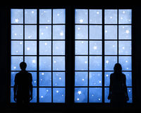 Couple looking through window at holiday background Stock Photo