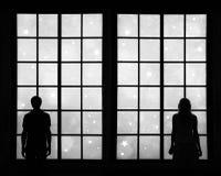Couple looking through window at xmas background Stock Photos