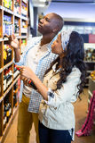 Couple looking at wine bottle in grocery section. At supermarket Stock Image