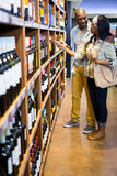 Couple looking at wine bottle in grocery section. At supermarket Stock Images