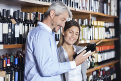 Couple Looking At Wine Bottle's Label Stock Photo