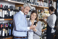 Couple Looking At Wine Bottle In Store Stock Photo
