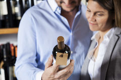 Couple Looking At Wine Bottle's Label Stock Photography