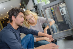 Couple looking at woodburner in store. Couple looking at a woodburner in a store Royalty Free Stock Images