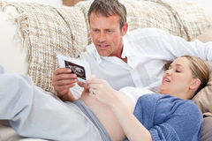 Couple looking at an X-ray on their couch Stock Photos