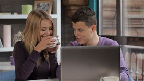 Couple looks at the laptop at the cafe. Young caucasian couple looking at the laptop screen at the cafe. Fit man dressed in violet pullover showing something on stock video footage