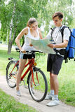 Couple looks at the map. Traveler asks for directions from a cyclist Royalty Free Stock Photos
